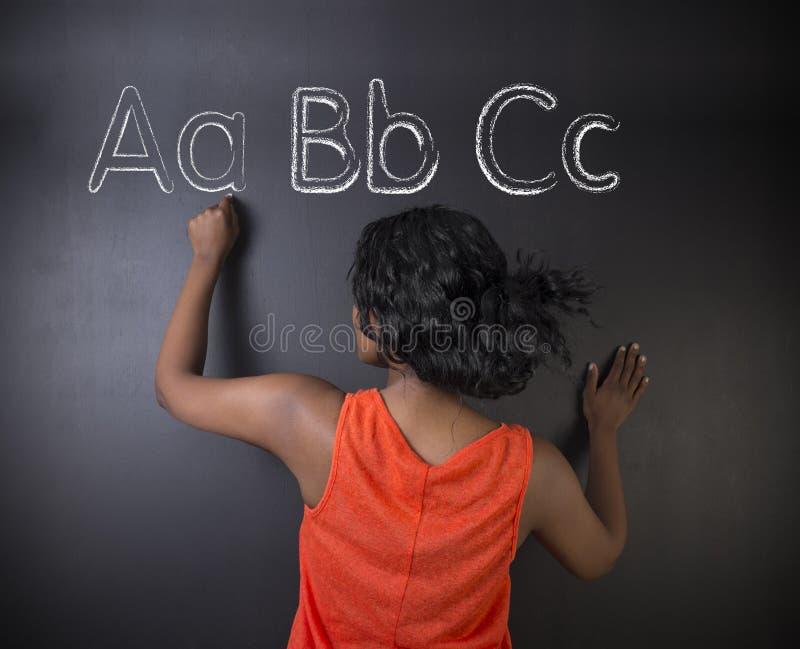 L'insegnante sudafricano o afroamericano o lo studente della donna impara che l'alfabeto scrive la scrittura fotografia stock libera da diritti
