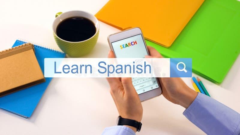 L'insertion de personne apprennent l'expression espagnole sur la barre de recherche de smartphone, leçons en ligne photographie stock