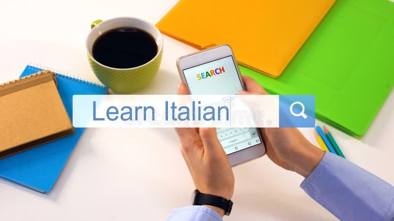 L'insertion de personne apprennent l'expression italienne sur la barre de recherche de smartphone, éducation en ligne photos stock