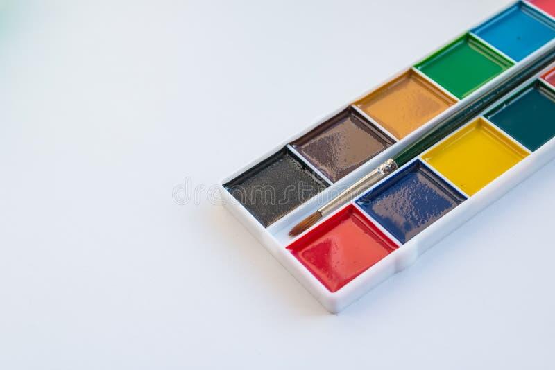 L'insieme completo delle pitture di colore di acqua su un fondo bianco Colori dell'acquerello in una scatola di plastica Insieme  fotografia stock