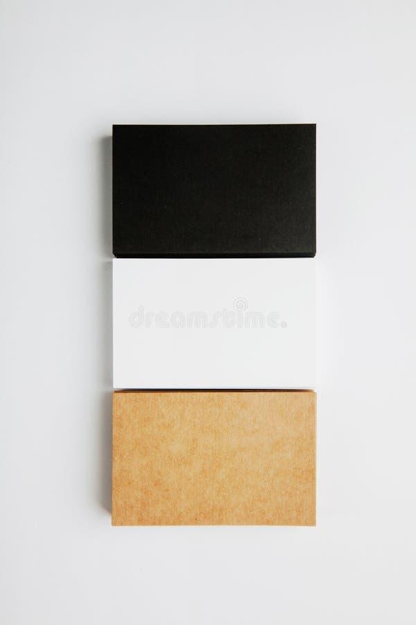 L'insieme dei biglietti da visita dello spazio in bianco della pila annerisce, bianco, mestiere su fondo bianco verticale fotografia stock libera da diritti