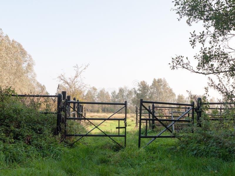 L'insieme del paese nero del campo dell'azienda agricola gates vuoto ed aperto fotografie stock