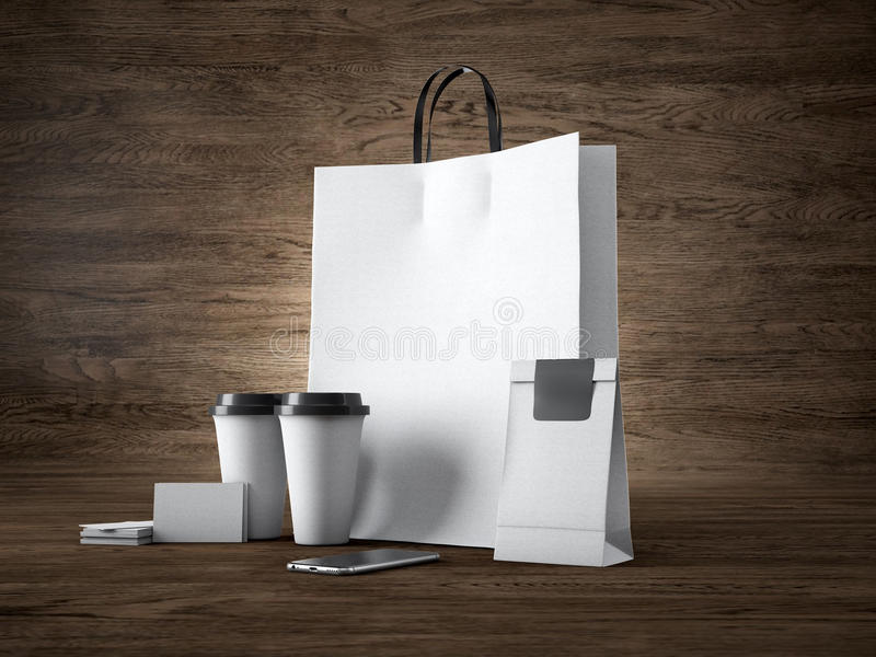 L'insieme del sacchetto della spesa bianco, porta via le tazze, il pacchetto di carta, i biglietti da visita in bianco e lo smart fotografia stock