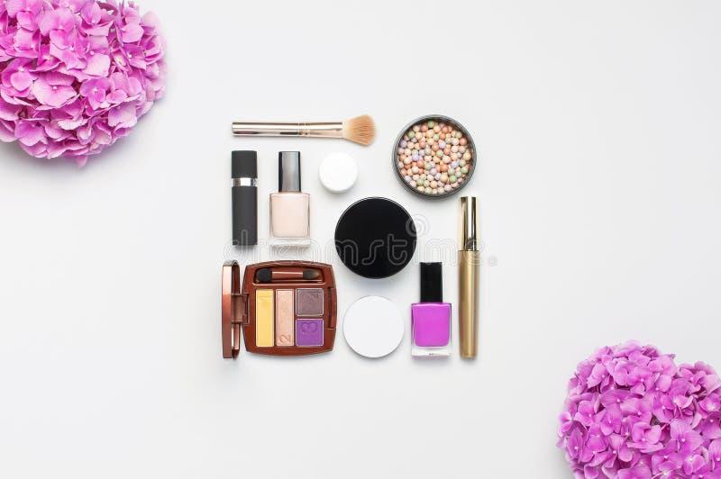 L'insieme dell'ombretto decorativo del rossetto della polvere della mascara dei cosmetici arrossisce fiori dell'ortensia di rosa  fotografie stock