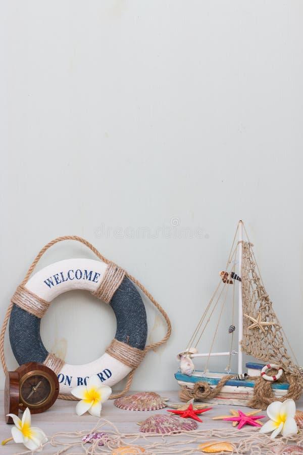 L'insieme della barca, la rete da pesca, le stelle marine e le conchiglie stanno su un fondo grigio chiaro Giovani adulti fotografie stock libere da diritti
