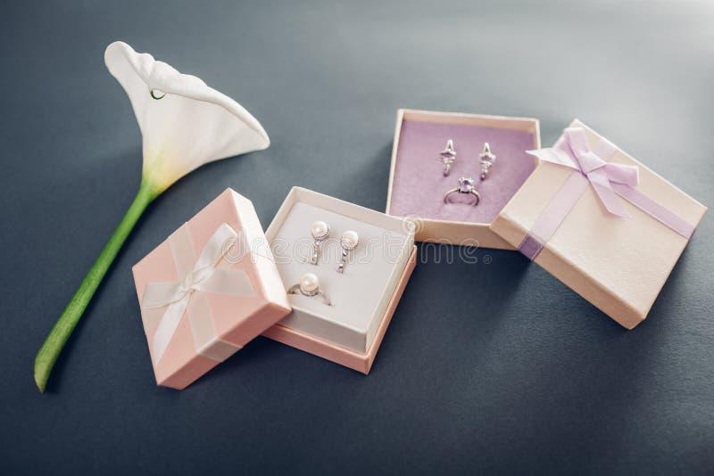 L'insieme della perla e dei gioielli di ametista in contenitori di regalo con il giglio fiorisce immagine stock