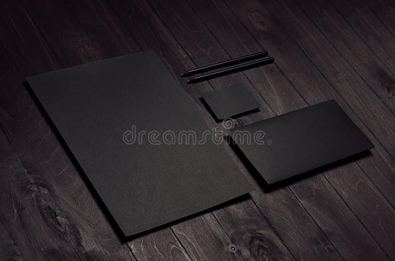 L'insieme di identità corporativa della carta intestata nera in bianco, la busta, biglietto da visita sul bordo di legno scuro, s immagini stock