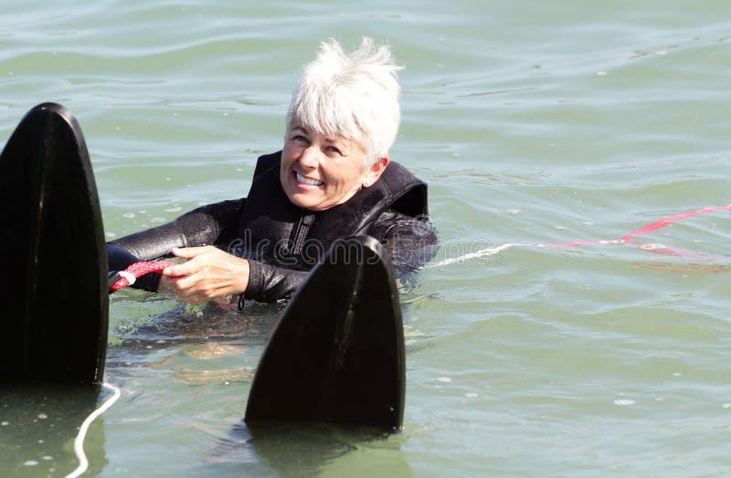 L'insieme pronto va. Corsa con gli sci della signora più anziana acqua. Copi lo spazio. fotografia stock