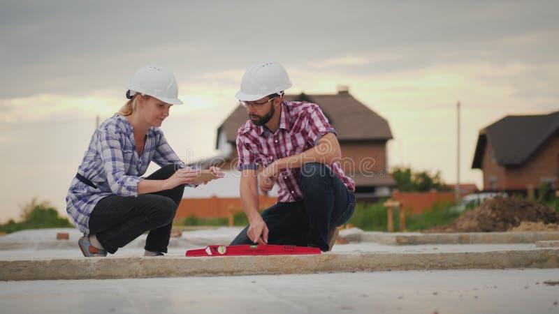 L'inspecteur de contrôle de qualité photographie les lectures du dispositif sur le chantier de construction Construction de quali image stock