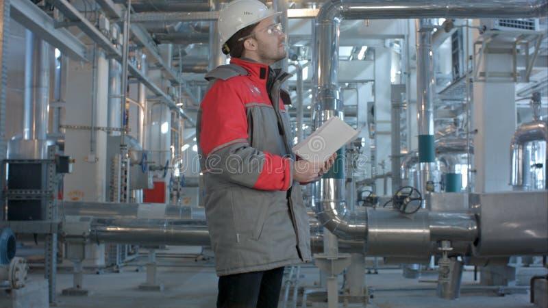 L'inspecteur mécanique fait l'inspection sur une usine images libres de droits