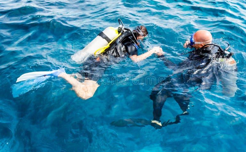 L'instructeur expérimenté de plongeur enseigne un plongeur de débutant à plonger en Egypte photographie stock libre de droits