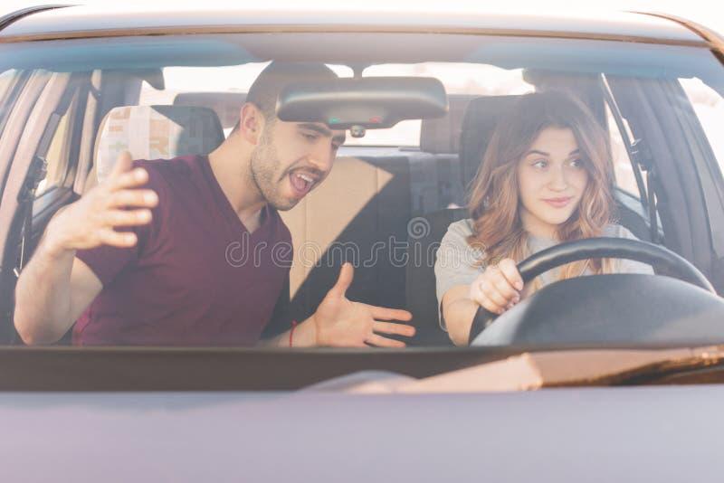 L'instructeur masculin d'examen de conduite enseigne la voiture femelle inexpérimentée d'entraînement de stagiaire, commande tout images libres de droits