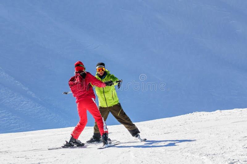 L'instructeur masculin enseigne le ski à une jeune femme un jour ensoleillé sur le fond neigeux de pente photo stock