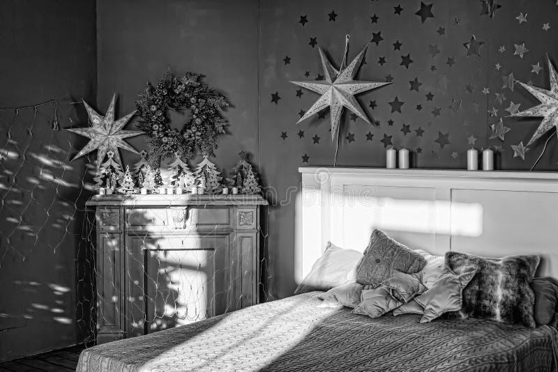 L'intérieur d'année noire et blanche et nouvelle Chambre à coucher avec la cheminée décorée des étoiles de Noël Maison douce image libre de droits