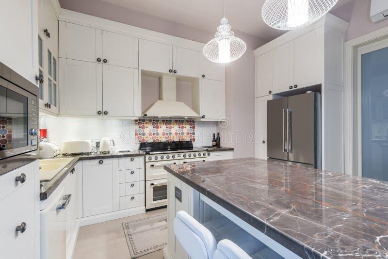 L'intérieur de cuisine avec l'île, évier, a couvert de tuiles des planchers dans nouveau photos stock