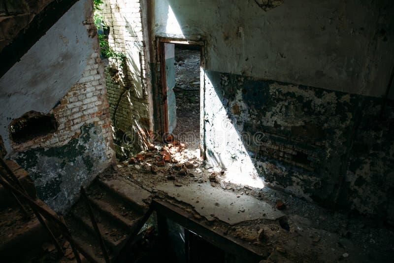 L'intérieur de l'obscurité ruiné a abandonné le bâtiment, porte au soleil photographie stock