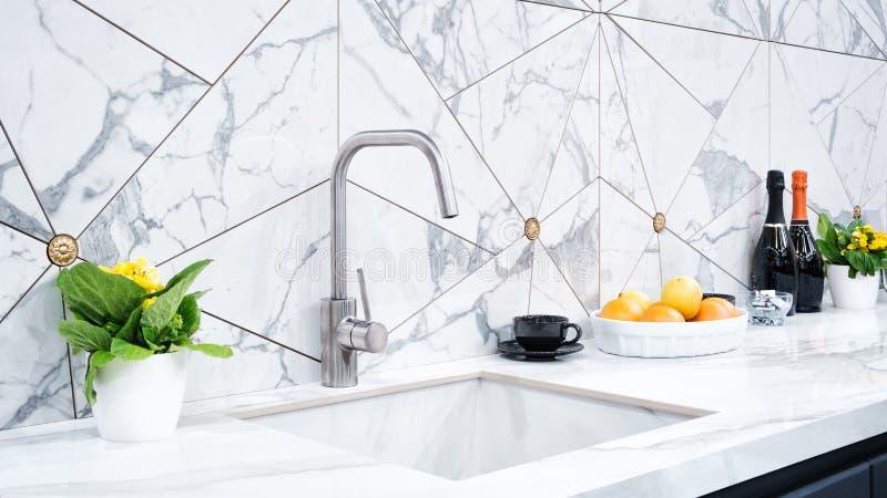 L'intérieur de la cuisine moderne est illuminé avec une partie supérieure du comptoir en pierre grise avec un lavabo de luxe images stock