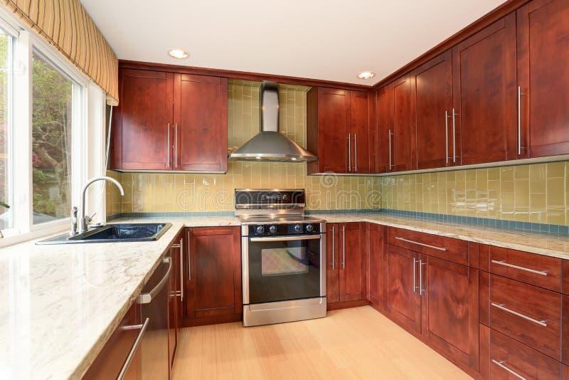 L'intérieur de pièce de cuisine avec les coffrets et la lumière bruns modernes modifie la tonalité le plancher en bois dur images libres de droits