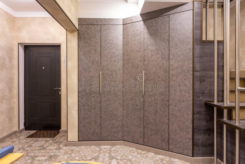 L'intérieur est un couloir spacieux, avec de grands cabinets et un escalier au deuxième plancher image stock