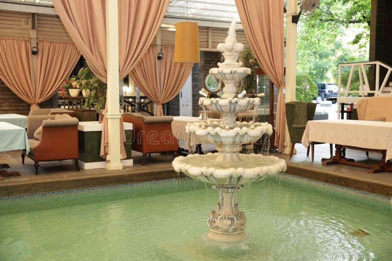 L'intérieur luxueux du restaurant avec une belle fontaine avec des bouteilles de champagne dans la fontaine image stock