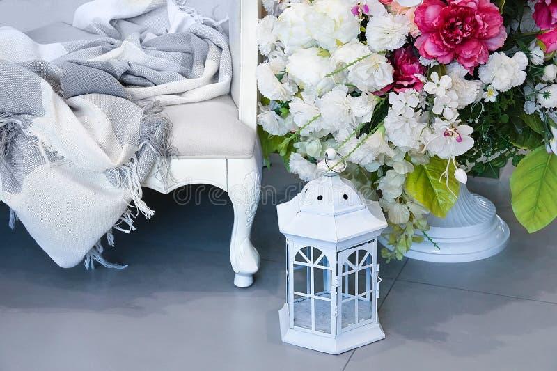 L'int?rieur de la salle Sofa blanc avec une couverture, les fleurs dans un vase et la lanterne blanche pour une bougie photographie stock libre de droits