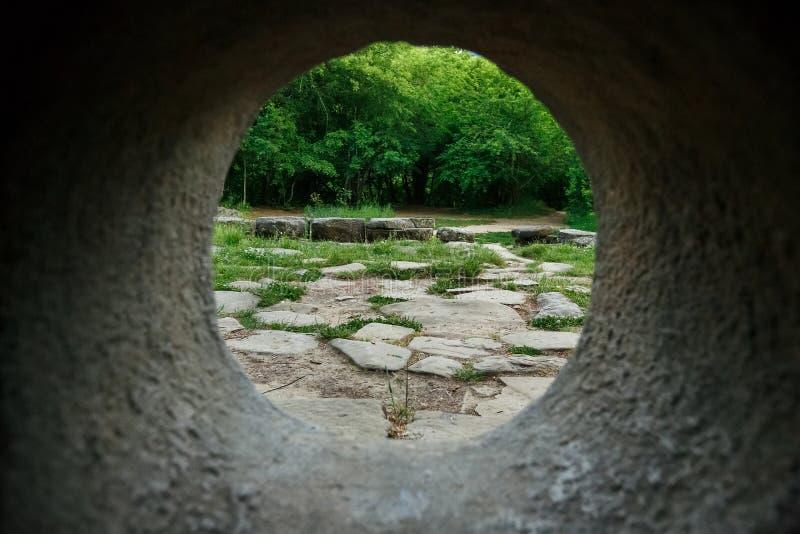 ? l'int?rieur de la vue d'un dolmen en pierre par un trou dans une for?t de montagne dans la vall?e de la rivi?re Jean photo libre de droits
