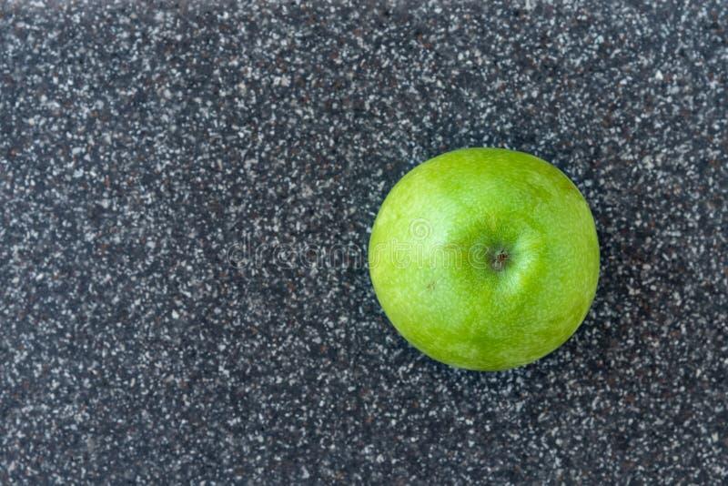 L'intera mela di Smith di nonna su un uomo di plastica ha reso a faux il tagliere grigio del granito immagine stock