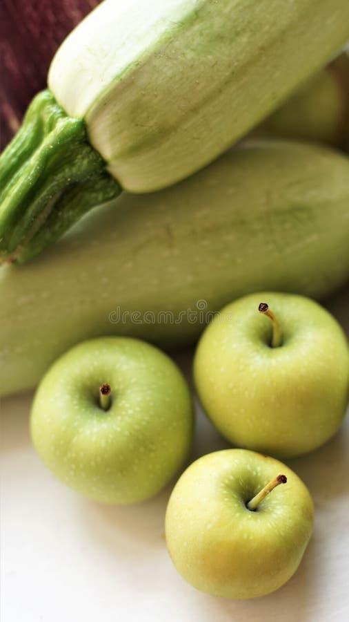 L'intere zucca e mele mature si trovano sul davanzale immagine stock