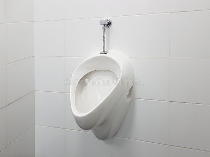 L'interno del bagno è allineato con le piastrelle di ceramica bianche Orinale ceramico ovale Luogo pubblico per i bisogni facenti fotografia stock