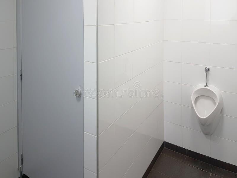 L'interno del bagno è allineato con le piastrelle di ceramica bianche Orinale ceramico ovale Luogo pubblico per i bisogni facenti fotografia stock libera da diritti