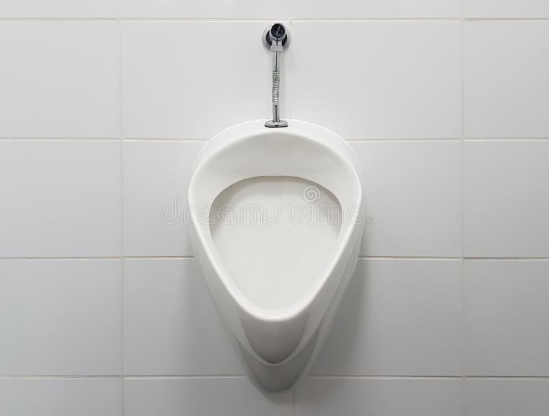 L'interno del bagno è allineato con le piastrelle di ceramica bianche Orinale ceramico ovale Luogo pubblico per i bisogni facenti immagine stock