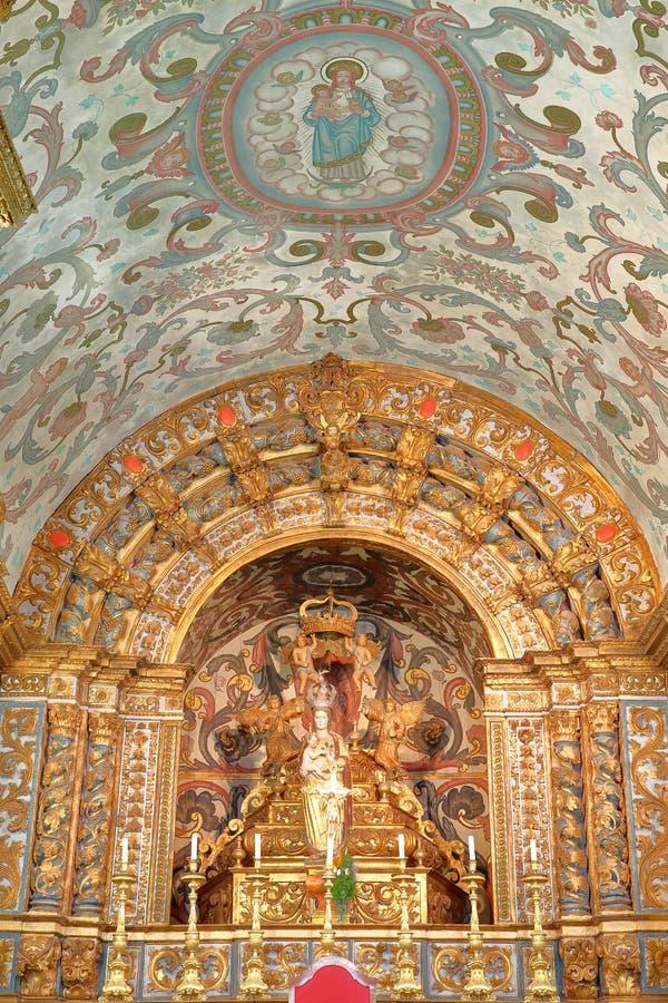 L'interno della chiesa Igreja Matriz di Vila do Bispo, con stile barrocco e una statua di vergine Maria immagini stock