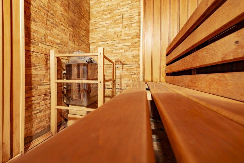 L'interno di una sauna di legno tradizionale con la stufa dei banchi e una siviera fotografia stock libera da diritti