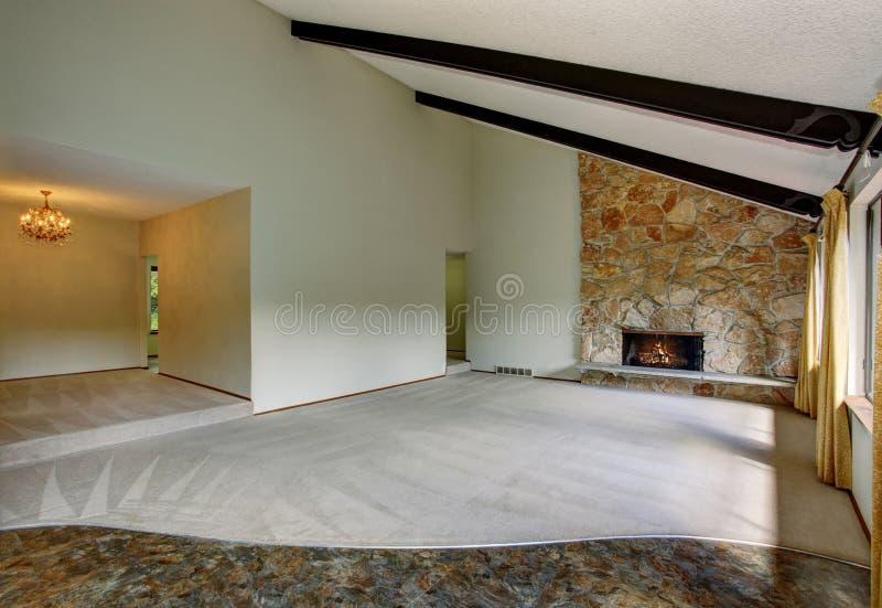 L'interno non ammobiliato spazioso del salone con il soffitto arcato alto e la pietra sistemano il camino fotografia stock