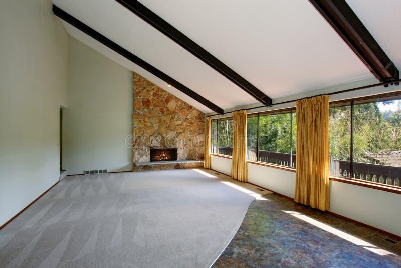 L'interno non ammobiliato spazioso del salone con il soffitto arcato alto e la pietra sistemano il camino immagine stock