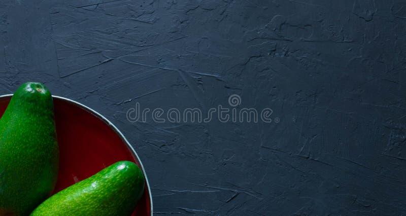 L'intero avocado si trova su un piatto fatto a mano Il concetto della frutta e delle verdure sane di cibo Vista da sopra Spazio p immagini stock libere da diritti