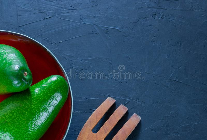 L'intero avocado si trova su un piatto fatto a mano Il concetto della frutta e delle verdure sane di cibo Vista da sopra Spazio p fotografia stock