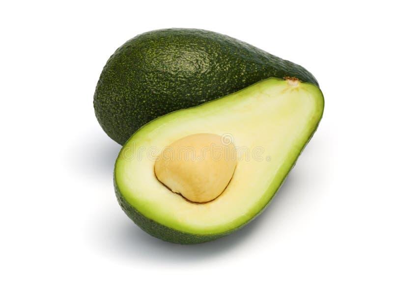 L'intero ed avocado diviso in due ha isolato fotografie stock libere da diritti