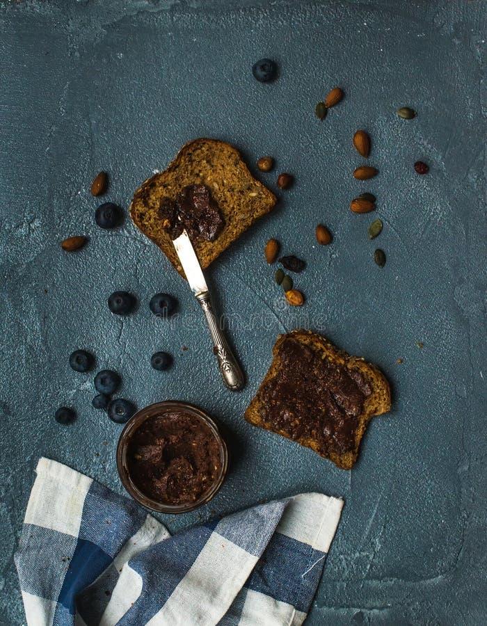 L'intero pane del grano tosta con il burro di arachidi organico del cioccolato del vegano, il mirtillo, dadi sopra il contesto di fotografie stock libere da diritti