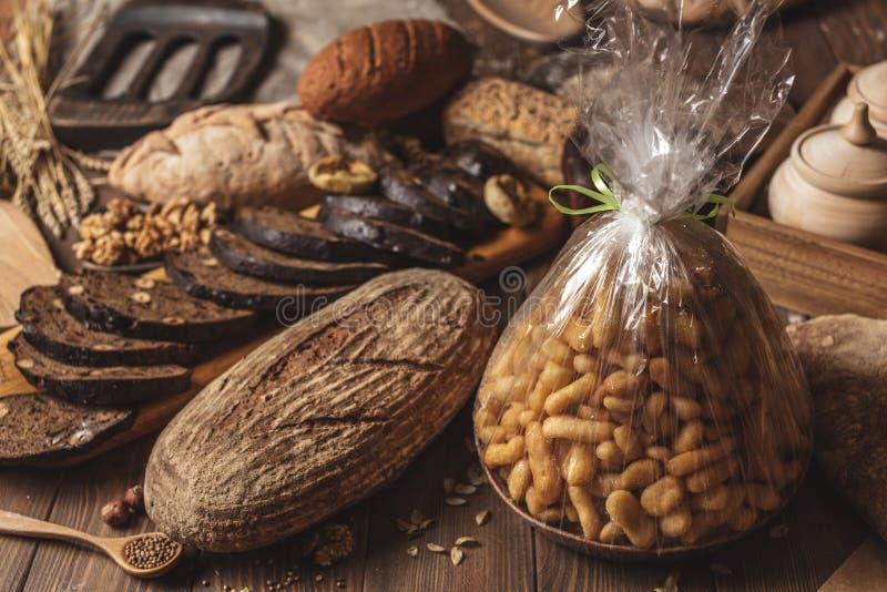 L'intero pane del multigrain del grano, intero ed affettato, contiene i semi isolati sul nero fotografia stock