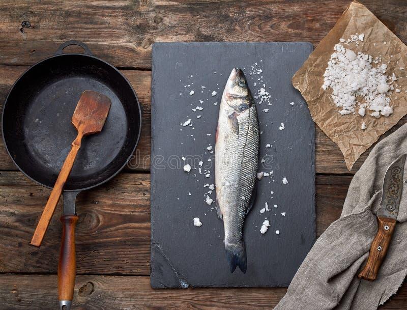 l'intero pesce fresco del branzino su un bordo nero della grafite, accanto è una padella vuota del nero del giro fotografia stock