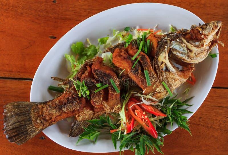 L'intero pesce fritto è servito con i peperoncini freschi affettati, cipolle verdi ed il basilico è servito in un ristorante in K fotografie stock libere da diritti