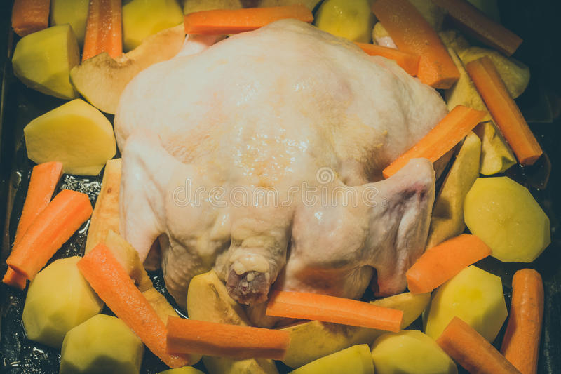 L'intero pollo fresco con frutta e le verdure è preparato per il co fotografia stock