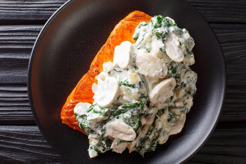 L'intero raccordo di color salmone è cotto alla perfezione, quindi ha finito con una guarnizione della fine degli spinaci, dei fu fotografia stock