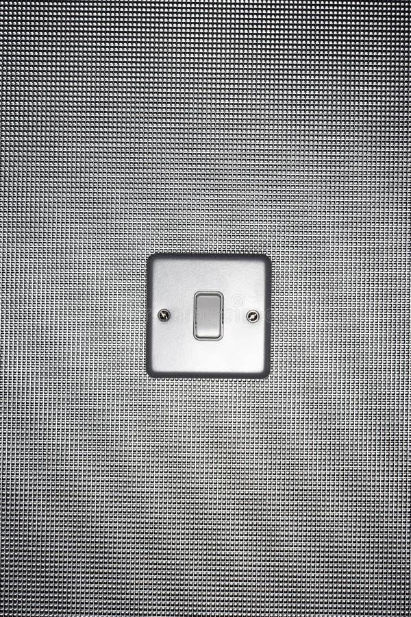 L'interrupteur de lampe argenté sur le papier peint a couvert le mur image libre de droits
