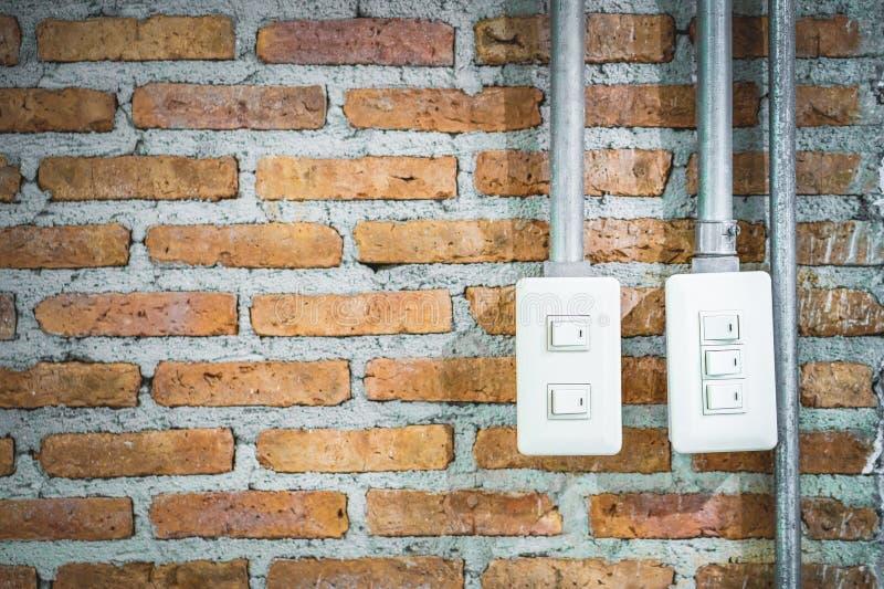 L'interrupteur de lampe et le métal électroniques sifflent sur le mur de briques rouge copie photos libres de droits
