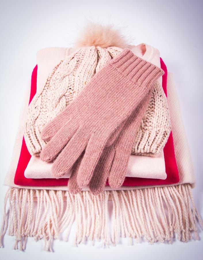 L'inverno caldo ha tricottato i vestiti - il cappello, la sciarpa, guanti su un fondo bianco immagini stock