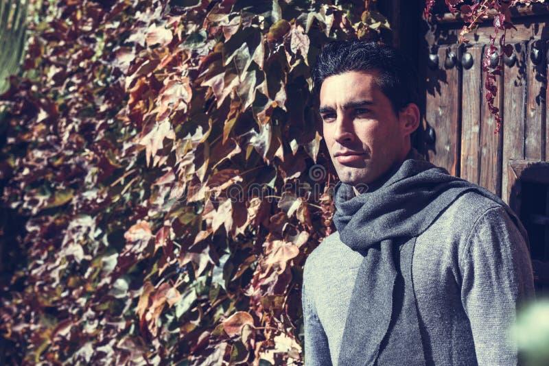 L'inverno d'uso dell'uomo bello copre del fondo di legno fotografia stock libera da diritti