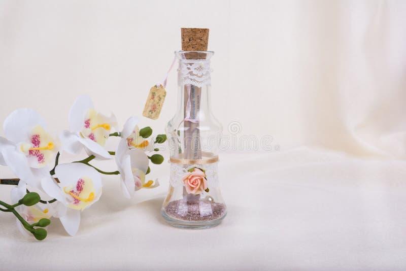 L'invito di nozze in bottiglia di vetro ed in orchidea fiorisce fotografie stock libere da diritti