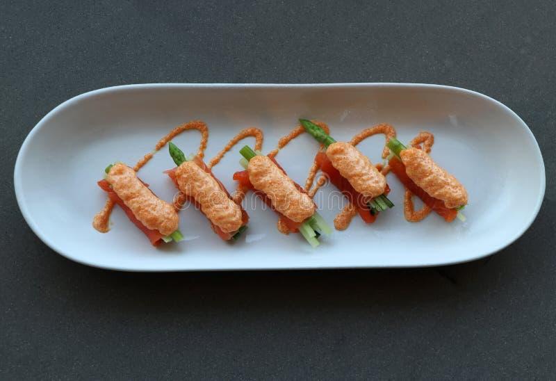 L'involucro di color salmone del raccordo sulle verdure dell'asparago e versa con le uova del pesce messe nel piatto ovale bianco fotografia stock libera da diritti